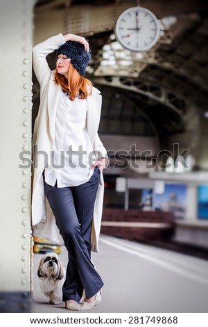 Elegant ginger hair woman and shih tzu dog on the platform under the clock waiting train at the Vitebsk railway station. Image with selective focus