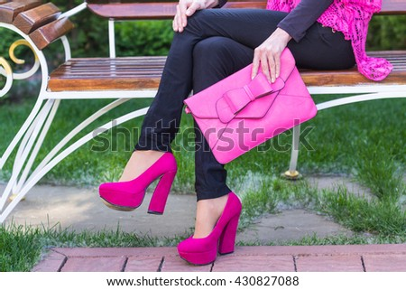 Elegant girl in crimson shoes with clutch in hand closeup - stock photo