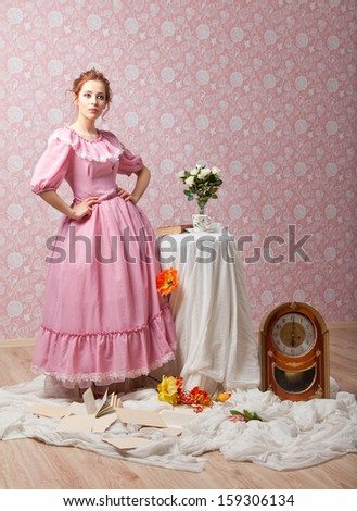 Elegant girl in pink clothes is standing near table with flowers - stock photo