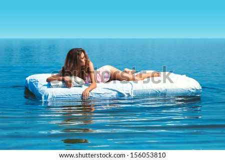 elegant girl lying on bed in open sea at daylights - stock photo