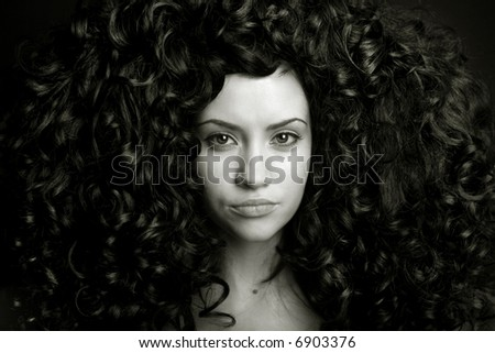 Elegant girl with magnificent curly hair. Studio portrait.