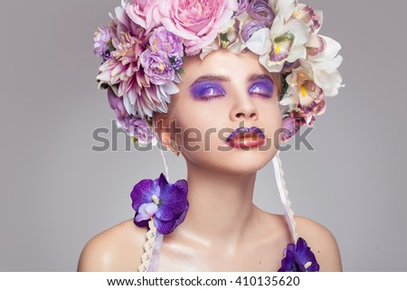Elegant Girl with wreath on head and makeup in purple tones and closed eyes in studio on grey background