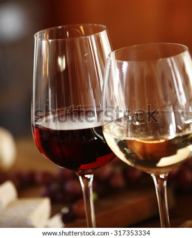 Elegant glasses of red and white wine served together on a dining table for a formal meal, close up of the bowls of the wineglasses and the wine - stock photo