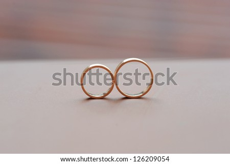 elegant golden rings on pink surface - stock photo