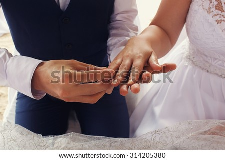elegant gorgeous bride and groom  in the tropical bungalow with wedding rings, hawaiian decor, on the background of  the ocean and a beach, wedding ceremony in Seychelles - stock photo