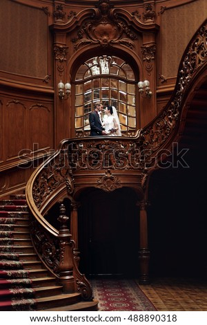 elegant gorgeous bride and stylish groom hugging, romantic moment. standing on wooden stairs in rich room. unusual wedding couple in retro style.