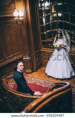 elegant gorgeous bride and stylish groom standing on wooden stairs in amazing old rich room. unusual wedding couple in retro style. luxury wedding concept. Man with long hair and piercing
