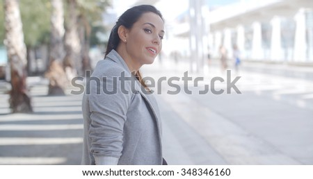 Elegant gorgeous young business woman sitting on a bench on a high key white modern urban promenade holding her long hair and smiling at the camera  with copyspace.