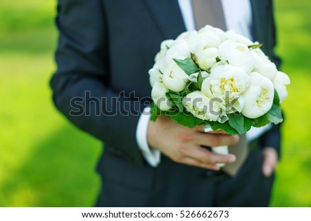 elegant groom dressed wedding tuxedo costume is waiting for the bride with bouquet of white peonies