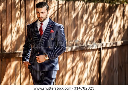 Elegant handsome man in classical blue suit poses near  wooden fence.