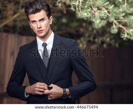 Elegant handsome man in classical suit poses near wooden fence. - stock photo