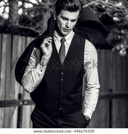 Elegant handsome man in classical suit poses near wooden fence. Black-white photo.