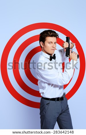 Elegant handsome man secret agent with a gun posing by a red shooting target. Spy man. - stock photo