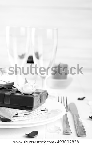 Elegant holiday table setting with red ribbon gift on white background . Black white photo