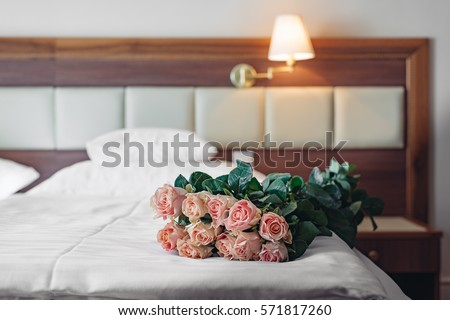 Elegant hotel room with a bouquet of roses. Romantic weekend concept.