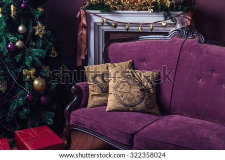 elegant interior Christmas decorations. Purple Sofa with two beige pillows stands next to a Christmas tree. Merry Christmas and happy New Year! A series of photos - stock photo