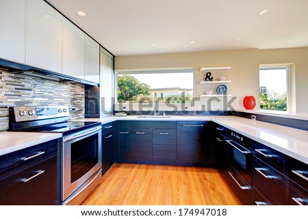 Elegant kitchen room with black wood storage combination with stoned backsplash and decorative vase and wall shelf - stock photo