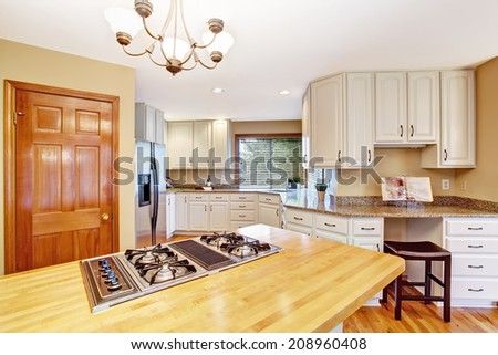 Elegant kitchen with white storage combination. View of kitchen island with built-in stove - stock photo