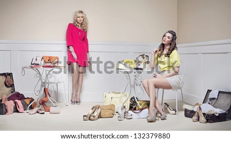 Elegant ladies in a room full of fashion accessories - stock photo
