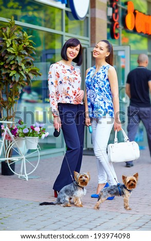 elegant ladies walking the dogs on city street - stock photo