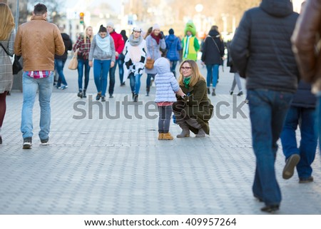 Elegant Lady and little Baby Girl walking on City Street among Crowd of People on Central Promenade on Weekend Springtime clothing Jacket and Coat Tenderness and Love concept