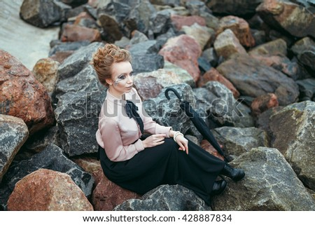 Elegant lady has a rest near the sea. She is sitting on a stone.