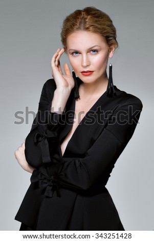 elegant lady in black suit with deep decollete touching her temple