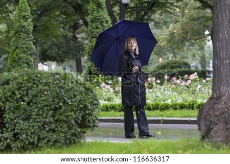 Elegant lady walking in a beautiful park under umbrella on a cold rainy day