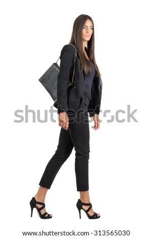 Elegant Latin business female in black suit and handbag walking side view.  Full body length portrait isolated over white studio background.  - stock photo