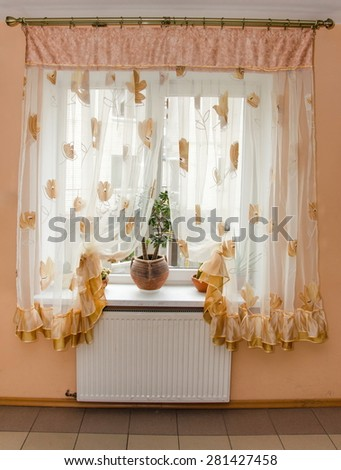 elegant light curtains (tulle) on the window in the kitchen - stock photo