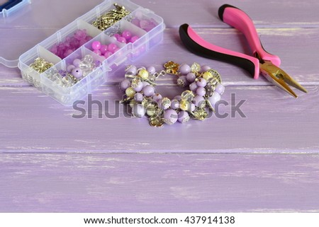 Elegant lilac bracelet made of acrylic beads and metal decorative elements. Stylish accessory for girls and women. Different beads and materials in a plastic box, pliers. Set for handmade jewelry  - stock photo