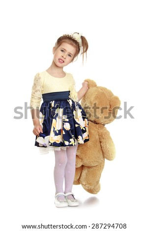 Elegant little girl in a beautiful gown that hugs a Teddy bear-Isolated on white background - stock photo
