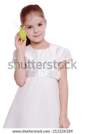 Elegant little girl in holiday dress holding colorful Easter eggs on white background