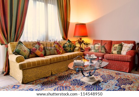 Elegant living room with classic looking sofa, colorful curtains, lamp and glass table