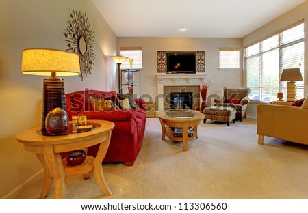 Elegant living room with red sofa, fireplace, TV and many windows. - stock photo