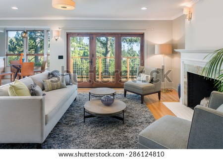 Elegant Living room with rug, fire place, couch, french doors and view windows. - stock photo