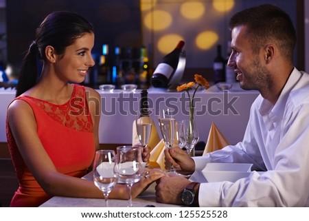 Elegant loving couple having dinner in restaurant, smiling happy. - stock photo