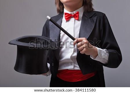 Elegant magician holding magic hat and wand - closeup - stock photo