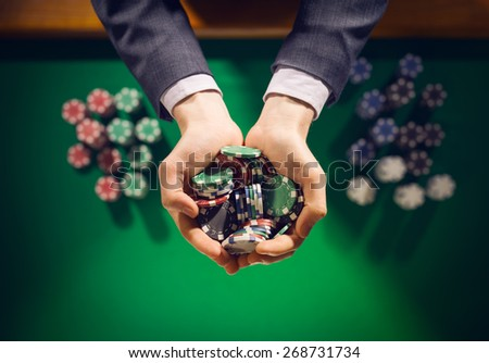 Elegant male casino player holding a handful of chips with green table on background, hands close up top view - stock photo