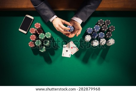 Elegant male poker player with smartphone holding chips, he has two ace cards, hands close up top view - stock photo