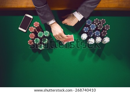Elegant male poker player with smartphone looking at his cards with piles of chips all around - stock photo
