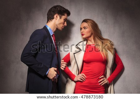 elegant man and woman looking at each other, man in suit and tie and woman in red dress