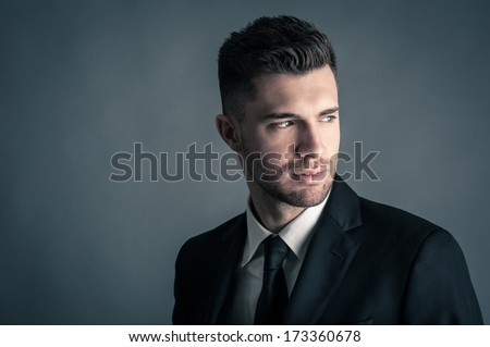 Elegant man close up portrait against dark background. - stock photo