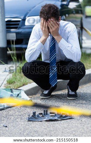 Elegant man crying at accident scene, vertical - stock photo