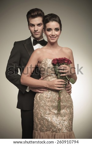 Elegant man holding his wife from the back while she is holding a bunch of red roses in her hands. - stock photo