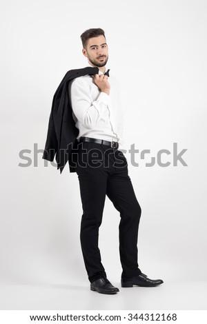Elegant man holding tuxedo coat over his shoulder looking at camera. Full body length portrait over gray studio background. - stock photo