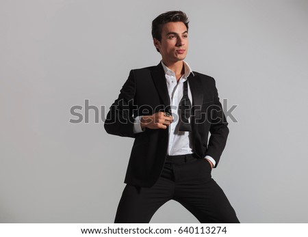 elegant man holding tuxedo's collar and looks to side on grey background