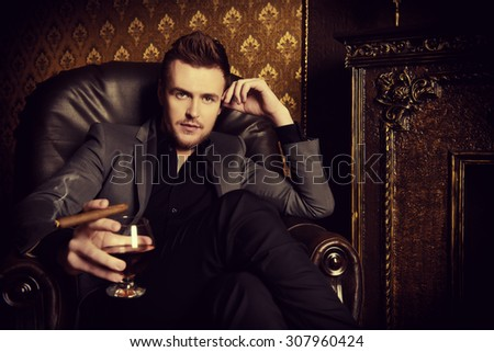 Elegant man in a suit with glass of beverage and cigar in vintage room. Fashion. - stock photo