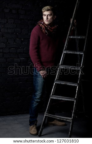 Elegant man in a sweater, jeans and a scarf standing near a ladder against a brick wall