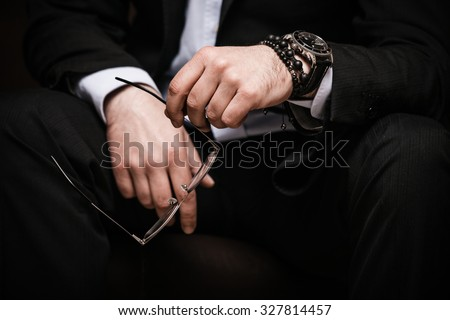 elegant man in black suite and white shirt hold eyeglasses in hand wearing watch and bracelet indoor shot selective focus closeup